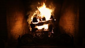 A roaring fire within a large stone arched fireplace. stock video footage