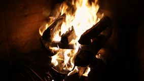 A roaring fire within a large stone arched fireplace. stock footage