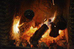 Roaring Log Fire and Grill. A roaring log fire in a fireplace with protective grill Stock Photo