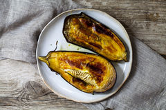 Roast aubergine on the plate. Roast aubergine on stoneware plate from above Stock Image