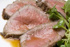 Roast beef. Four slices of tasty roast beef with its sause Royalty Free Stock Photo