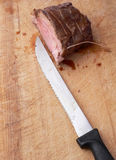 Roast beef. A slice of roast beef on a wood plate whit a long knife apart Stock Photography