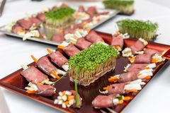 Roast beef appetizers on porcelain plate royalty free stock photos