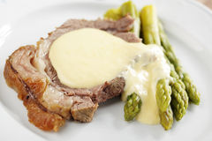 Roast beef and asparagus. Under cheese sauce stock images