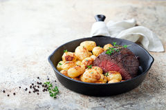 Roast beef and baked potatoes in cast iron frying pan Stock Photo