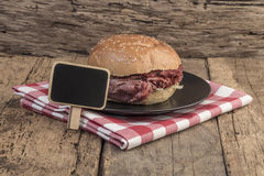 Roast beef burger and a chalkboard on wooden table Stock Photography