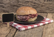 Roast beef burger and a chalkboard on wooden table Royalty Free Stock Photography