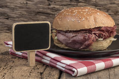 Roast beef burger and a chalkboard on wooden table Royalty Free Stock Photo