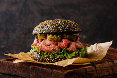 Roast beef Burger with sliced Pastrami and pickle. Roast beef Burger Takeaway snack on sesame bun with sliced Pastrami and pickle on black background Royalty Free Stock Photo