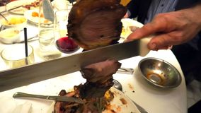 Roast beef cut slices. Close up of a picanha roast beef cut on the spit in Brazilian steak house. Brazilian restaurant with sword stock video
