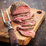 Roast beef. On cutting board and meat fork Stock Photos