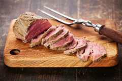 Roast beef. On cutting board and meat fork Stock Image