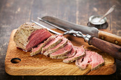 Roast beef. On cutting board with saltcellar and meat fork royalty free stock photography