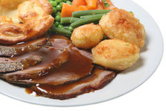 Roast Beef Dinner. Roast beef with Yorkshire pudding, vegetables and gravy Royalty Free Stock Photo