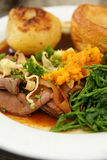Roast beef dinner. British roast beef dinner with roast potatoes, Yorkshire pudding and vegetables mashed swede and samphire Stock Image