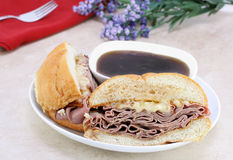 Roast Beef Dip Sandwich. Delicious roast beef dip sandwich with onions, melted cheese and plenty of dipping sauce stock photography