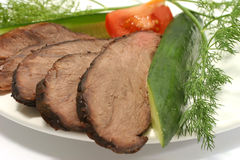 Roast beef on dish. Sliced roast meat on dish with vegetables Stock Photo