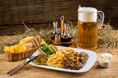 Roast beef, french fries and jug of beer Royalty Free Stock Photography
