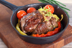 Roast beef in a frying pan. With vegetables, tilt shift Stock Image
