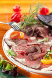 Roast beef with horseradish. Tomatoes and herbs royalty free stock photography
