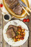 Roast beef joint with roast vegetables Royalty Free Stock Images