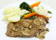 Roast beef with mushroom sauce. Roast beef with a mushroom gravy, served with boiled potatoes and steamed vegetables Stock Photo
