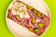 Roast Beef Open Faced Sandwich With Sliced Onions Gherkins and H. Orseradish Sauce On Rye Bread Against A Green Background Royalty Free Stock Photography