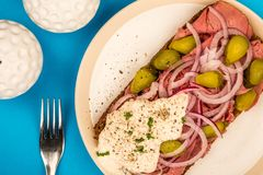 Roast Beef Open Faced Sandwich With Sliced Onions Gherkins and H. Orseradish Sauce On Rye Bread Against A Blue Background Stock Image
