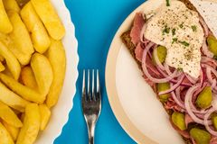 Roast Beef Open Faced Sandwich With Sliced Onions Gherkins and H. Orseradish Sauce On Rye Bread Against A Blue Background Royalty Free Stock Photography