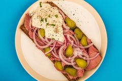 Roast Beef Open Faced Sandwich With Sliced Onions Gherkins and H. Orseradish Sauce On Rye Bread Against A Blue Background Stock Images