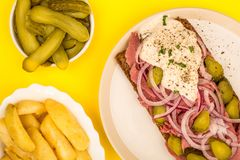 Roast Beef Open Faced Sandwich With Sliced Onions Gherkins and H. Orseradish Sauce On Rye Bread Against A Yellow Background Stock Photos