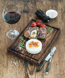 Roast beef Ossobuco with rice, vegetables and glass of wine on serving board over rustic wood background Royalty Free Stock Image