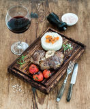 Roast beef Ossobuco with rice, vegetables and glass of wine on serving board over rustic wood background Royalty Free Stock Photography