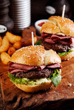 Roast beef or pastrami burger on a sesame bun. With salad trimmings on a wooden counter in a fast food restaurant for a delicious snack or pub lunch Stock Photo