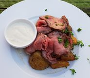 Roast beef on a plate of American potatoes royalty free stock photography
