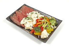 Roast beef with potato salad and vegetables Stock Image