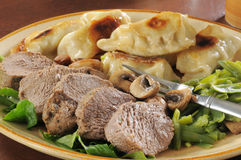 Roast beef and potstickers. A plate of roast beef and potstickers with green beans Royalty Free Stock Photography