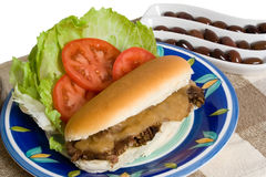 Roast Beef Roll and Salad over white background. Hot roast beef and gravy roll with lettuce and tomato over white background Royalty Free Stock Photo