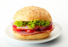 Roast Beef Sandwich. Es with Lettuce, Tomatoes and Red Onions on a white plate Royalty Free Stock Photography