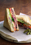 Roast beef sandwich. With tomato, lettuce placed on a sheet of parchment paper Royalty Free Stock Image