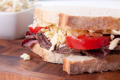 Roast beef sandwich with cheese and tomato. Sliced roast beef sandwich with cheese and tomato and cole slaw Stock Photography
