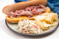 Roast beef sandwich and cole slaw. Deli style sliced rare roast beef on a roll with cheese, cole slaw and chips Royalty Free Stock Image