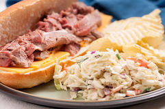 Roast beef sandwich and cole slaw. Deli style sliced rare roast beef on a roll with cheese, cole slaw and chips Royalty Free Stock Photos