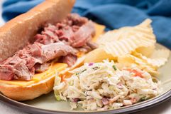 Roast beef sandwich and cole slaw. Deli style sliced rare roast beef on a roll with cheese, cole slaw and chips Stock Photos