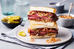Roast beef sandwich on a plate with pickles. Stock Image