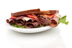 Roast beef sandwich on rye bread. Delicious roast beef sandwich platter with whole wheat bread and potato chips Royalty Free Stock Images