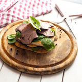 Roast beef sandwich with salad and pepper on rustic wooden plate. Stock Photo