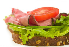Roast beef sandwich on white, close up. Roast beef sandwich with lettuce, tomatoes, cucumbers and radishes isolated on white background Stock Photo