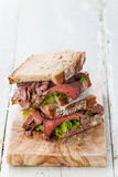 Roast beef sandwiches. With lettuce on olive wood cutting board Stock Photography