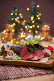 Roasted Wagyu Beef Sirloin. Rare roast Wagyu beef sirloin with slices of fruits on a wooden board, christmas theme Stock Image